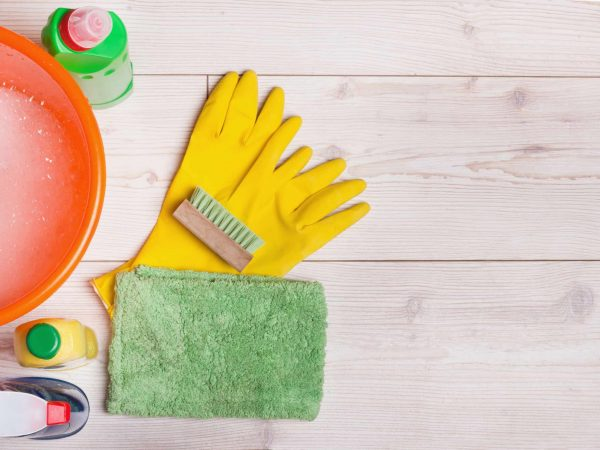 Top view of cleaning supplies and tools for house keeping on the bright laminate floor