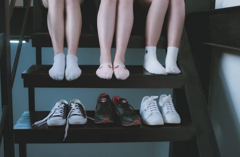 Personen in Socken auf Treppe. Schuhe stehen eine Stufe darunter