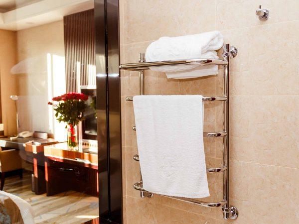 Modern heated towel rail on tiled in hotel.