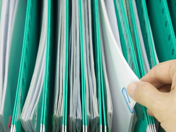 Hand of man pick paperwork of receipt and report with colorful paperclip from green suspension folder hang in cabinet.