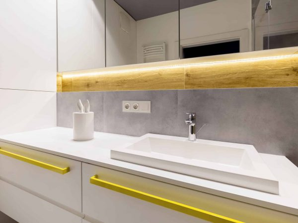 Close-up of white cabinet with yellow accents in modern bathroom interior with wood and mirror