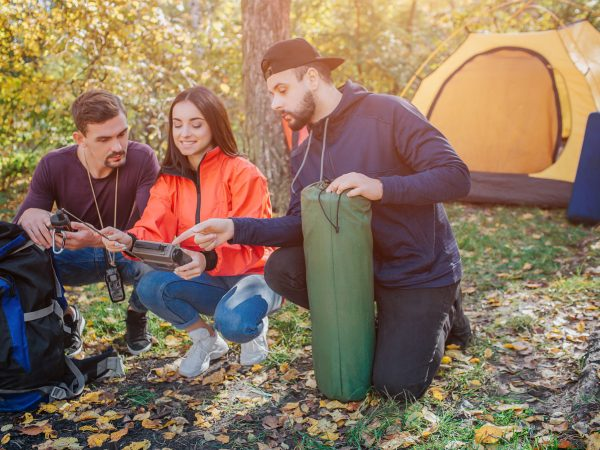 Three friends sit in squad position and look at radio young woman holds. Bearded guy holds sleeping bag. Another young man has knife in cover. They talk