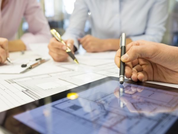 Business team desk architect man woman digital tablet blueprint construction