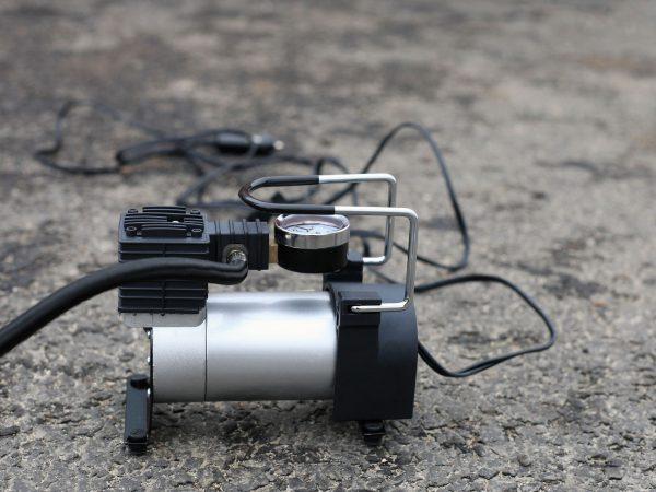 Tire inflator car tool on road. Portable metal air compressor pump for car wheels, driver equipment