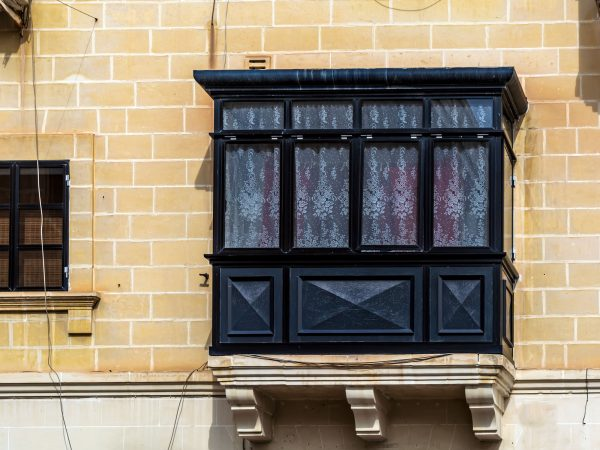 Traditional Maltese enclosed wooden balcony painted in black with white lace curtains in Cospicua (Bormla), Malta. Authentic Maltese urban scene.