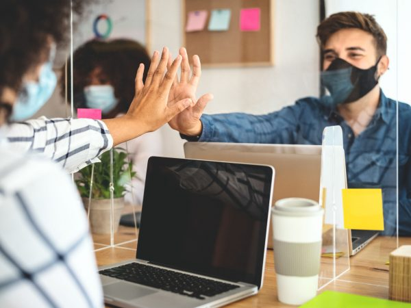 Young people in co-working creative space wearing surgical mask protection and keeping social distance to avoid corona virus spread – Health care and business technology concept