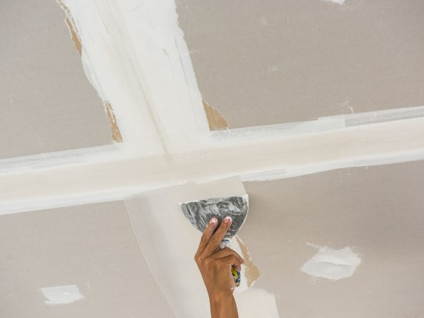 50334847 – man hand with trowel plastering a ceiling, skim coating plaster walls