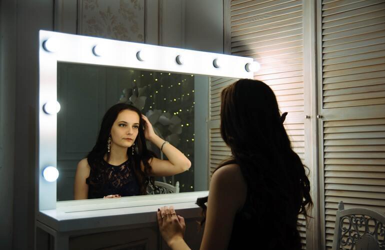 Frau, die sich in einem großen Kosmetikspiegel mit Beleuchtung betrachtet.