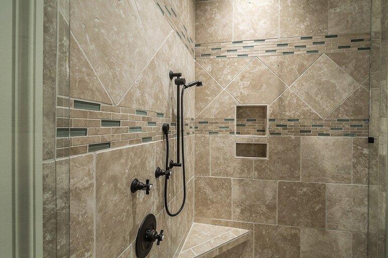 Eine Dusche mit verschiedenen Fließen an den Duschwänden