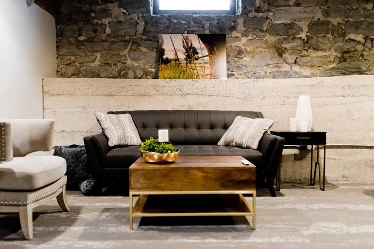 Ein Couchtisch in Holzoptik und goldenem Gestell, welcher vor einer schwarzen Couch steht, auf der zwei beige Polster liegen.
