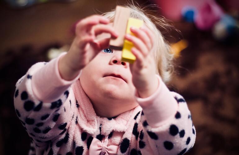 Das Bild zeigt ein weibliches Kleinkind, das mit Holzblöcken spielt.