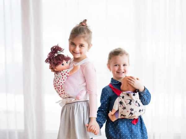 A portrait of two small girls standing and carrying dolls in baby carriers indoors, holding hands.