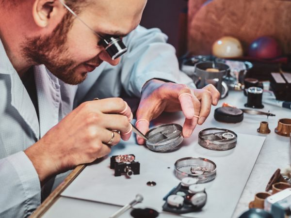 Expirienced clockmaster is fixing old watch for a customer at his repairing workshop.