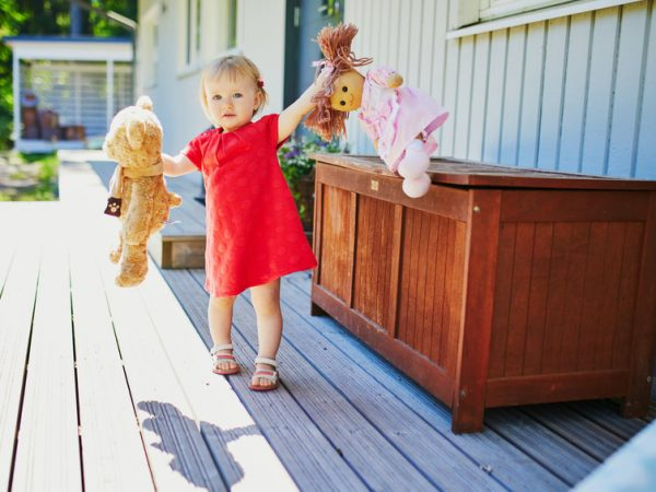 Adorable baby girl in red dress playing with doll and teddy bear outdoors on a sunny summer day. Little child having fun. Kid playing stuffed toys