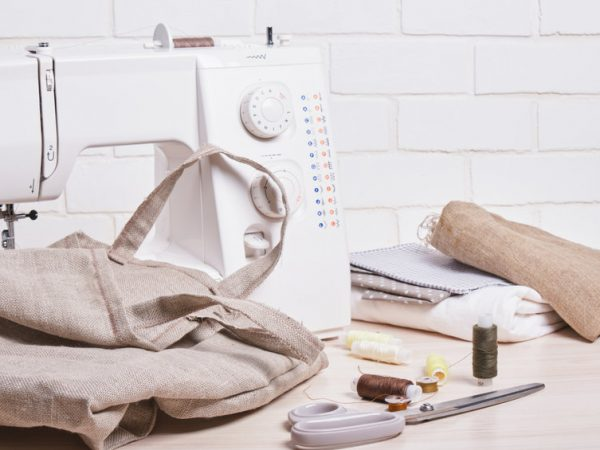 the process of sewing eco bags, thread, scissors and a sewing machine on the background of a white brick wall copy space