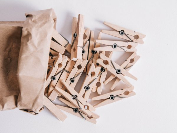 Wooden clothespins in paper bag on white background. View from above. Place for your text.