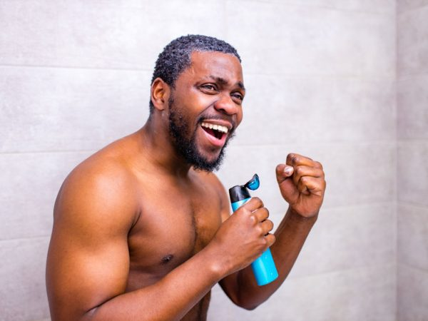 Attractive young cheerful man singing while washing in the shower, holding shampoo bottle like microphone.