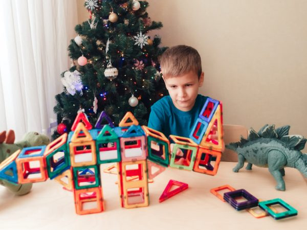 Child playing with magnetic constructor near by Christmas tree