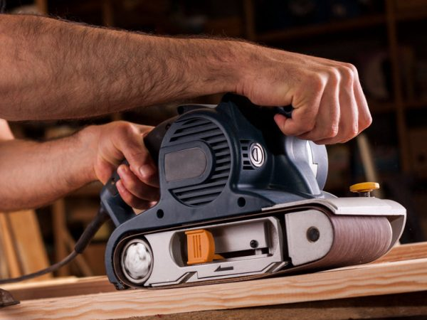 carpenter works with belt sander in carpentry