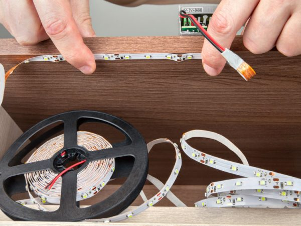 Close-up of a hand electrician, installation LED strip inside the cabinet.