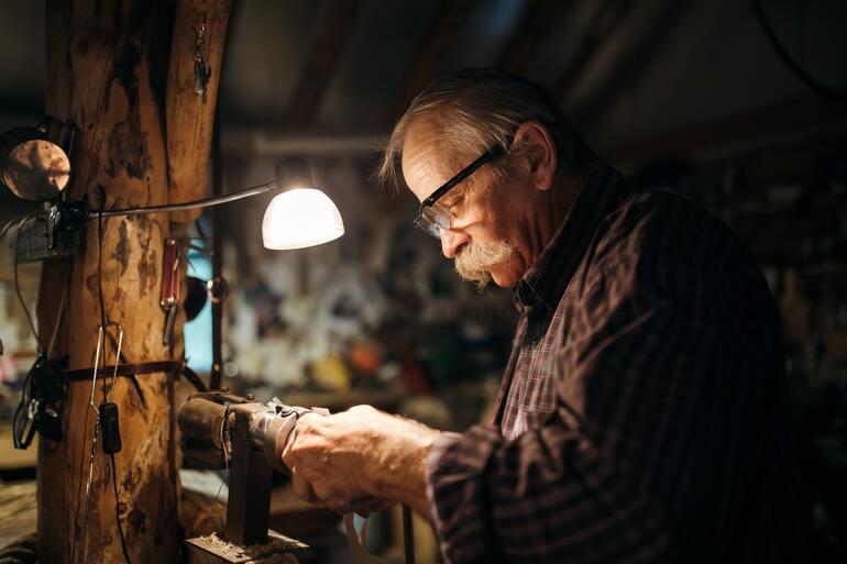Mann arbeitet in der Werkstatt mit einer Lampe