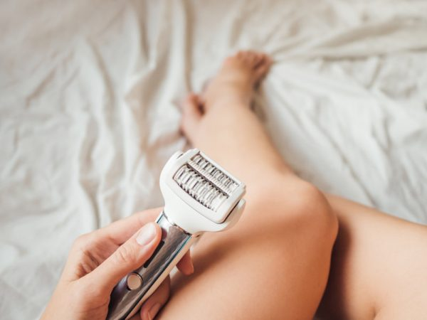 Woman takes care of herself, depilated legs with epilator. Epilation cosmetological procedure for hair removal. Spa at home. Skin care.