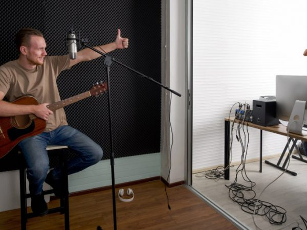 Young caucasian artist with acoustic guitar checks the correctness of the audio recorder before starting work with sound engineer. Musicians producing music in professional recording studio.